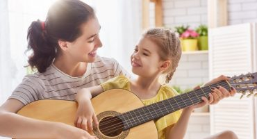Mutter mit Kind spielen zusammen Gitarre